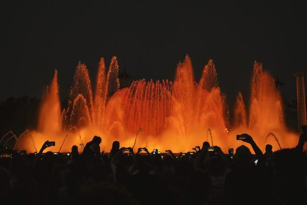 Fotografia sylwetki ludzi przed fontanną