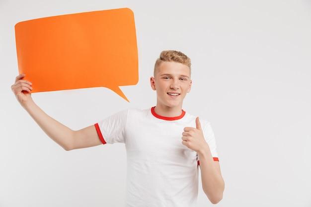 Fotografia szczęśliwa reklamodawca chłopiec jest ubranym przypadkowej koszulki mienia copyspace pomarańczowego plakat dla twój teksta i pokazuje kciuk up odizolowywającego na bielu
