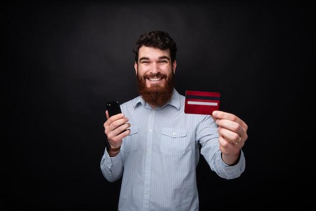 Fotografia szczęśliwy brodaty mężczyzna trzyma smartphone i shwing przy kamerą kredytową kartę, stoi nad ciemnym odosobnionym tłem