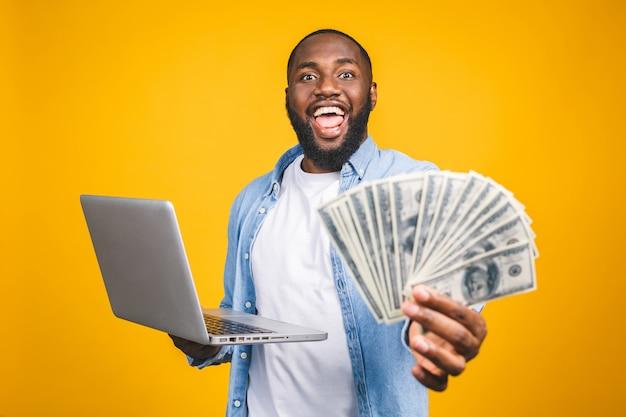Fotografia szczęśliwy młody afro amerykański przystojny mężczyzna pozuje używać laptopu mienia pieniądze.