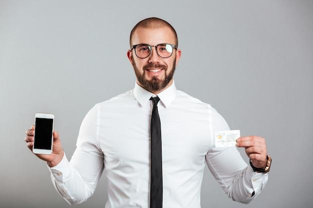 Fotografia szczęśliwy pomyślny mężczyzna w szkłach, krawata areszt przy sądzie telefon i kredytowa karta, odizolowywający nad szarości ścianą