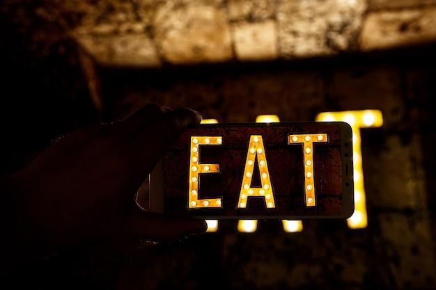 Fotografia telefonem komórkowym. obraz słowa jeść napisany przez żarówki.