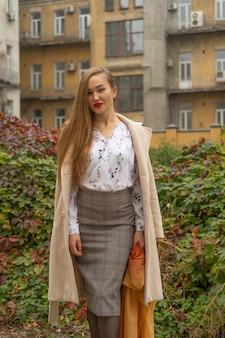 Fotografia uliczna młodej pięknej kobiety na sobie stylowe klasyczne ubrania. model patrzy w dół. koncepcja kobiecej mody.