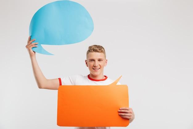 Fotografia uśmiechnięta reklamodawca chłopiec jest ubranym przypadkową koszulkę trzyma dwa copyspace bąbla dla twój teksta odizolowywającego na bielu