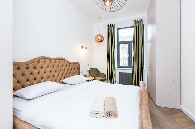 Fotografia wnętrz duża sypialnia z białym łóżkiem w nowoczesnym stylu