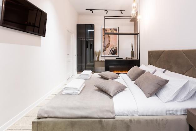 Fotografia wnętrz, nowoczesna sypialnia z dużym stylowym łóżkiem, nowoczesny design, w kolorze beżowym