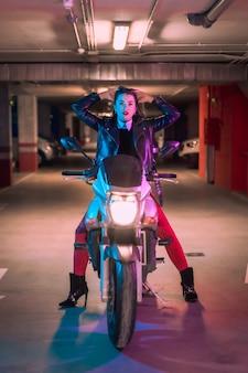 Fotografia z niebieskimi i różowymi neonami na motocyklu. młoda blondynka kaukaski modelka pozuje w czarnej skórzanej kurtce