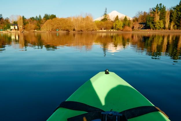 Fotografia z zielonego kajaka na środku spokojnego jeziora otoczonego naturalnym lasem i ośnieżonym wulkanem