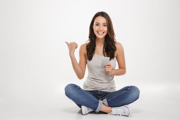 Fotografia zadowolona kobieta z długim brown włosianym obsiadaniem z nogami krzyżował na podłoga używać srebnego smartphone i wskazuje daleko od, odizolowywający nad biel ścianą