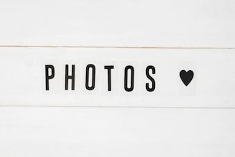 Fotografie tekst i czarny kierowy kształt na białym drewnianym tle