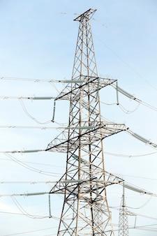 Fotografowane słupy elektryczne ustawione w dzień, chmury na niebie, budynki przemysłowe