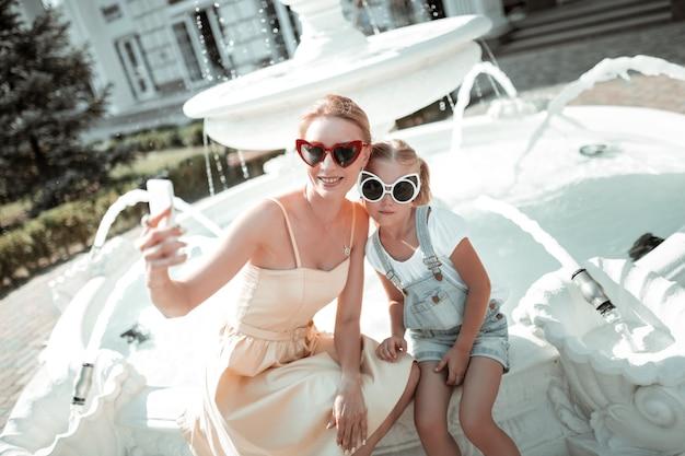 Fotografowanie chwili. szczęśliwa kobieta siedzi z córką na fontannie i robi selfie.