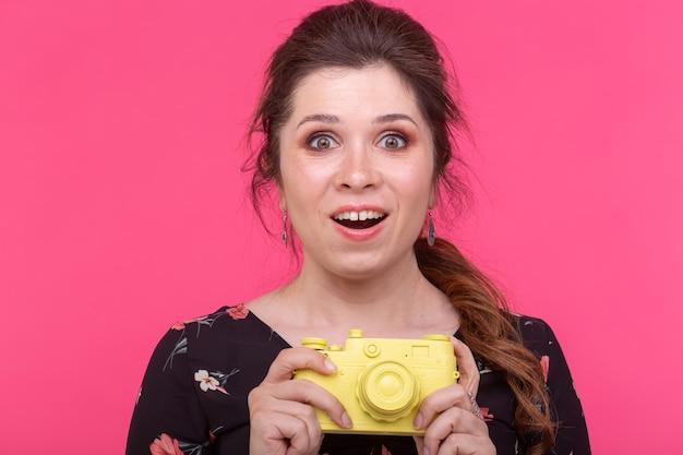 Fotografowanie, glamour i rocznika koncepcja - młoda kobieta z aparatem retro uśmiecha się