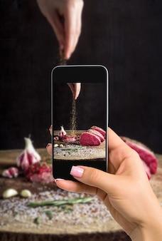 Fotografowanie koncepcji żywności - kobieta robi zdjęcie soczystego kawałka mięsa leżącego na drewnianej desce nożem rzeźniczym. ręka posypuje przyprawami