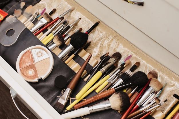 Fotografowanie w salonie kosmetycznym. migawka miejsca pracy wizażysty z rozłożonymi profesjonalnymi kosmetykami i pędzlami.