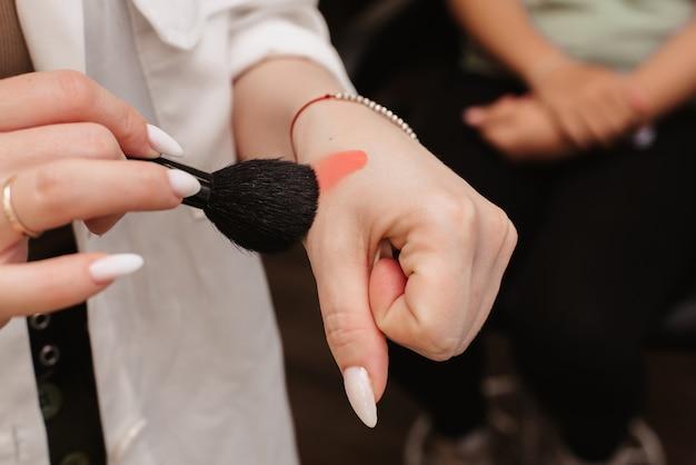 Fotografowanie w salonie kosmetycznym. zdjęcie przedstawiające dłonie wizażystki, która za pomocą pędzla wpisuje produkt kosmetyczny.