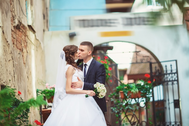 Fotografowanie weselne. panny młodej i pana młodego, spacery po mieście. małżeństwo obejmując i patrząc na siebie.