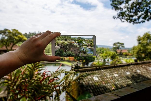 Fotografowanie ze smartfonem w ręku. koncepcja podróży. pałac na wodzie tirta gangga na bali.