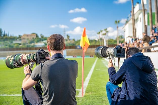 Fotografowie i dziennikarze sportowi zarejestrowani podczas gry na boisku piłkarskim