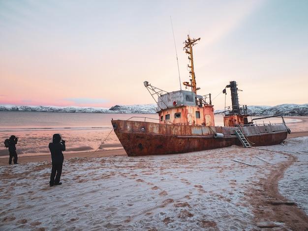 Fotografowie robią zdjęcia statku wyrzuconego przez sztorm na wybrzeżu oceanu arktycznego.