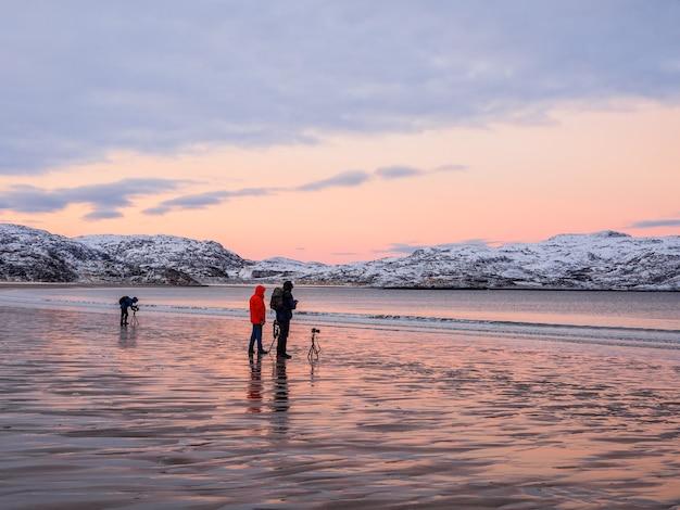 Fotografowie robią zdjęcia wspaniałego arktycznego krajobrazu o zachodzie słońca na oceanie arktycznym.