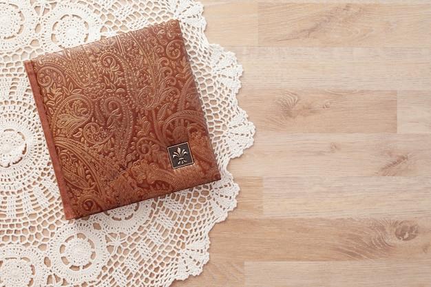 Fotoksiążka, notatnik lub pamiętnik z okładką z prawdziwej skóry. kolor brązowy z ozdobnym tłoczeniem. album zdjęć ślubnych lub rodzinnych. skopiuj miejsce
