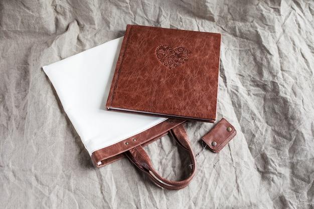 Fotoksiążka w okładce z prawdziwej skóry z tekstylną torbą.