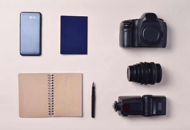 Fotoreporter. smartfon, notatnik, paszport, aparat fotograficzny. koncepcja podróży, widok z góry, płaskie świeckich