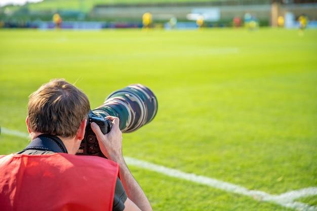 Fotoreporter z teleobiektywem na meczu piłki nożnej