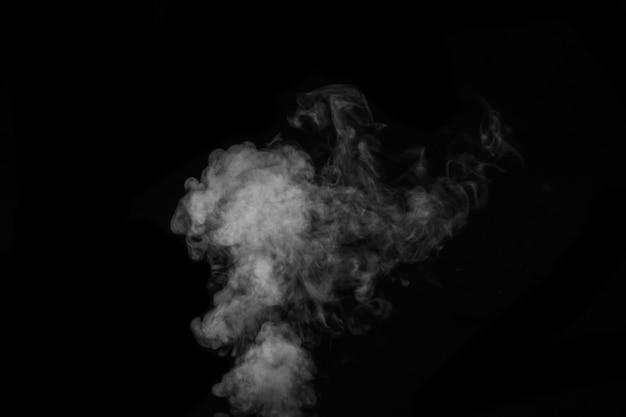 Fragment białego gorącego kręconego dymu parowego na białym na czarnym tle, zbliżenie. twórz mistyczne zdjęcia halloween. abstrakcyjne tło, element projektu