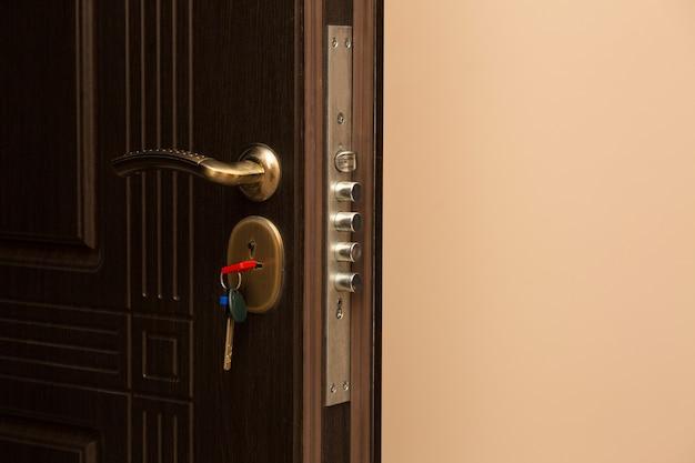 Fragment brązowych metalowych drzwi wejściowych z zamkiem i kluczem. miejsce na tekst
