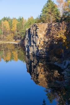Fragment brzegu jeziora z kamieniem w lesie jesienią wczesnym rankiem