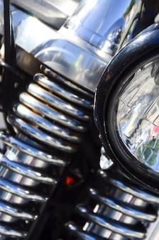 Fragment chromowanej błyszczącej lampy starego klasycznego motocykla