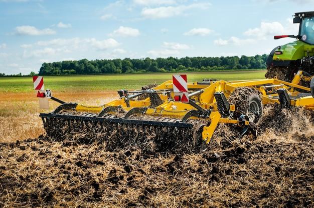 Fragment ciężkiej brony talerzowej, system uprawy roli w pracy na tle pola