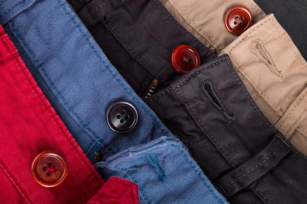 Fragment czterech spodni bawełnianych diagonalnych w kolorze czerwonym, niebieskim, czarnym, beżowym z rozpiętymi guzikami. ścieśniać.