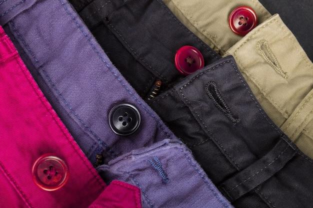 Fragment czterech spodni bawełnianych diagonalnych w kolorze czerwonym, niebieskim, czarnym, beżowym z rozpinanymi guzikami. ścieśniać.