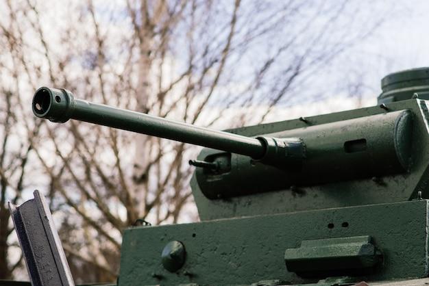 Fragment gąsienicy na zielonym czołgu w kamuflażu.