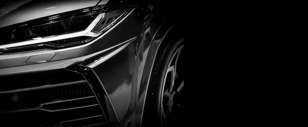 Fragment jednego z super samochodów z reflektorami led na czarnej ścianie, wolne miejsce na tekst po prawej stronie