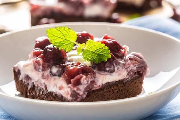 Fragment kawałka brownie z kremem, wiśniami i listkami świeżej mięty na talerzu.