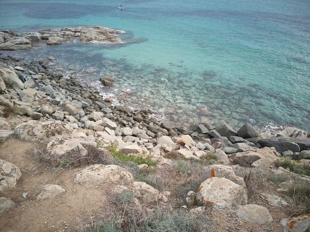 Fragment klifu, który wznosi się na przezroczyste morze na południowym wybrzeżu sardynii