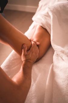 Fragment masażu fizjoterapeuty z tyłu lewej nogi młodej kobiety leżącej na stole. fizjologia, osteopatia, masaż relaksacyjny, film z zabiegu na plecach
