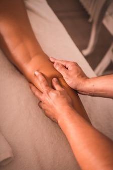Fragment masażu fizjoterapeuty z tyłu prawej nogi młodej kobiety leżącej na stole. fizjoterapia, osteopatia, masaż relaksacyjny, film z zabiegu na plecach