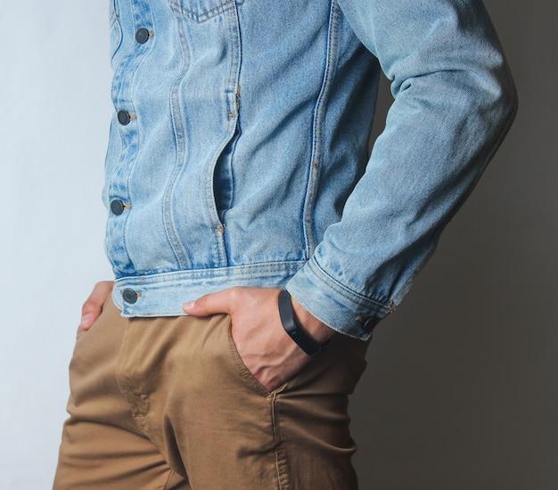 Fragment mężczyzny ubranego w jeansową kurtkę i beżowe spodnie.