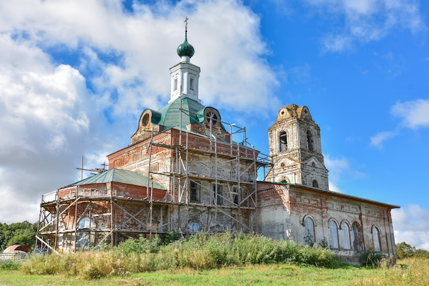 Fragment odrestaurowanego kościoła z nową kopułą na tle zachmurzonego nieba, otoczony zielenią, zbliżenie