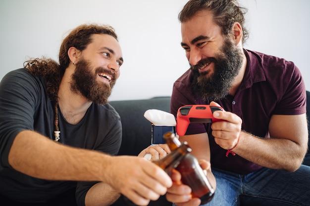 Fragment przedstawiający dwóch uśmiechniętych przyjaciół rozbijających butelki piwa i konsole do gier