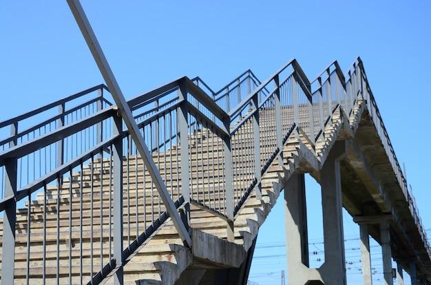 Fragment schodkowego wejścia na most dla pieszych między peronami dworca kolejowego