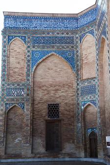 Fragment ściany ozdobionej mozaikami i ornamentami ze starożytnymi drewnianymi drzwiami w mauzoleum gur emir w samarkandzie w uzbekistanie. 29.04.2019