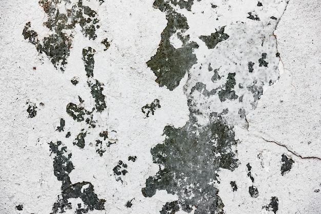 Fragment ściany z rysami i pęknięciami w tle