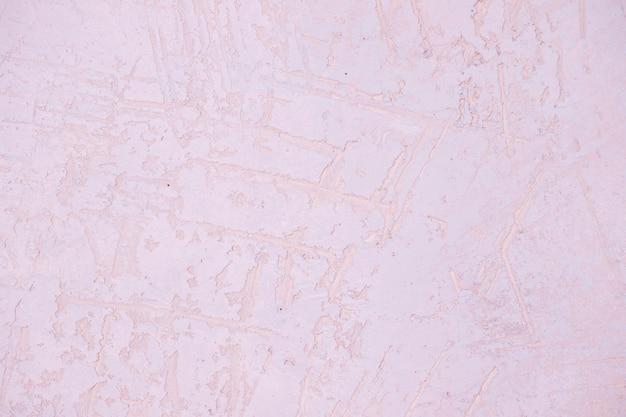 Fragment ściany z zadrapaniami i pęknięciami. jasny różowy tynk ściana tekstur. pastelowa ściana. streszczenie powierzchni ściany malowane. ściana sztukatorska z kopią dla projektu. betonowa faktura powierzchni ściany