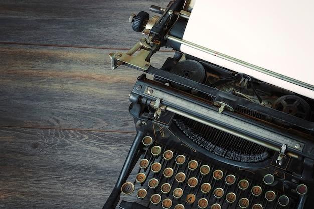 Fragment starej maszyny do pisania z białą kartką papieru